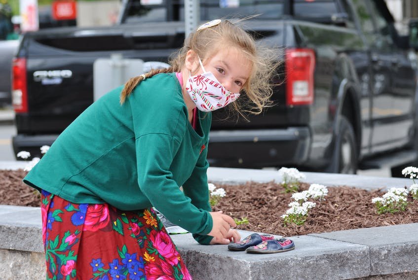 Marlee Lowe of Port Saunders circled the Mikwite'tm Garden on the Majestic Lawn in Corner Brook on Friday touching each of the pairs of children's footwear that have been left there over the past two weeks. The garden, an initiative of the Qalipu First Nation in honour of Missing and Murdered Indigenous Women and Girls, was officially opened Friday.