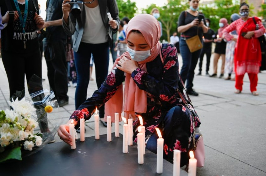 A woman places a candle during the vigil held in Montreal in memory of the family. Vigils were held across Canada, but a Muslim migrant worker in Halifax said systemic change is what's needed to protect marginalized communities, including Muslims, and acknowledge the discrimination they face.- Andrej Ivanov/Reuters