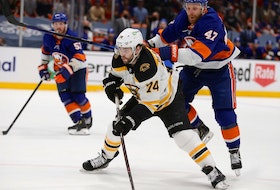 Boston Bruins left wing Jake DeBrusk (74) plays the puck against New York Islanders right wing Leo Komarov (47) during the third period of game six of the third round of the 2021 Stanley Cup Playoffs at Nassau Veterans Memorial Coliseum on June 9, 2021.