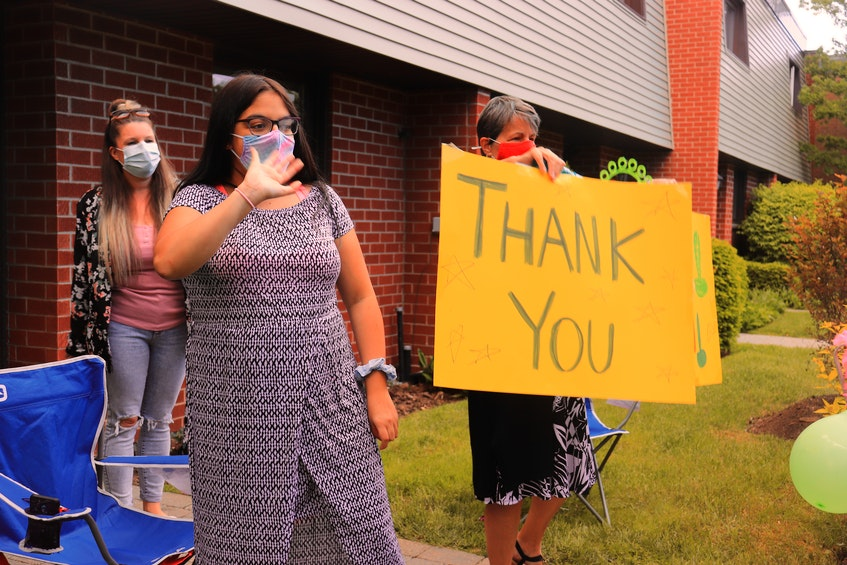 Tahlia Ali, 16, waves to her friends who drove by her temporary home in Halifax Sunday afternoon to welcome her back to Nova Scotia. Ali returned to the province last Thursday after being away for about a year in Toronto for a double lung transplant procedure. - Noushin Ziafati