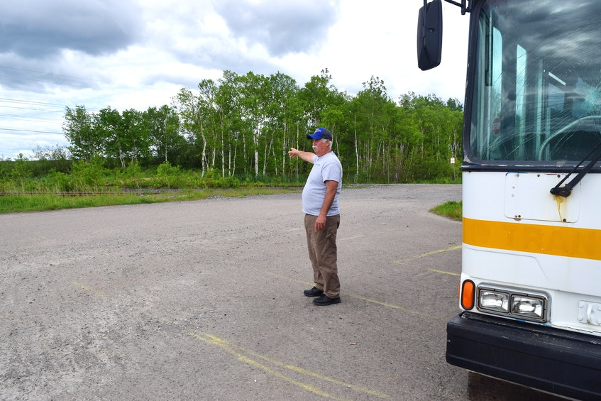 Gary Pozzebon, president of the Cape Breton Drag Racing Association, points to where the ATV trail comes out onto their property at former DEVCO wash plant facility on Grand Lake Road, in Sydney. Pozzebon said culprits smashed numerous windows out on their bus and as a result of ongoing vandalism and theft, they are having discussions about their land use agreement with local ATV clubs. Sharon Montgomery-Dupe/Cape Breton Post. - Sharon Montgomery