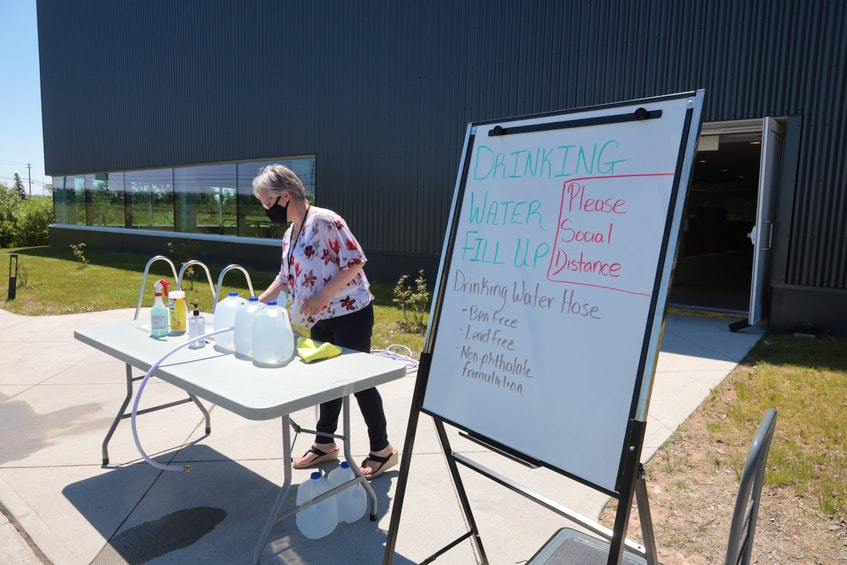 Carla Countway, aquatics co-ordinator with the Municipality of East Hants, cleans up after a busy morning of handing out water Monday to those affected by the shut down of accessibility to the Shubenacadie Grand Lake water system. - ERIC WYNNE/CHRONICLE HERALD