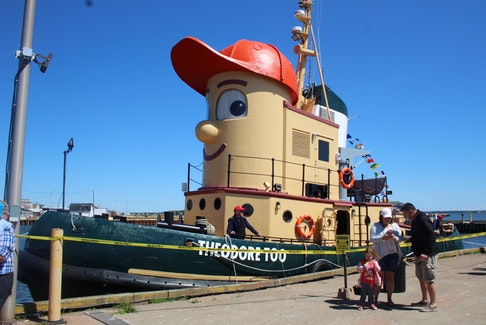 Laurie Simm, a deckhand aboard the Theodore Too, welcomes a family in Summerside, P.E.I., on June 12. Theodore Too Tugboat was the star of a CBC children's television show for several years  and the character's real-world likeness worked as a tour boat in the Halifax Harbour for many more. Theodore recently bid Halifax fairwell and is now on his way to his new home in Hamilton, Ont. He made a stop in Summerside on his farewell tour through the Maritimes.