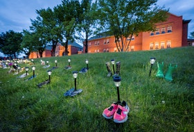 Pairs of children's shoes and toys are seen at a memorial in front of the former Kamloops Indian Residential School after the remains of 215 children, some as young as three years old, were found at the site in Kamloops, B.C. REUTERS