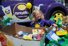 Nevaeh's cousin two-year-old Juliana Denine, also got in on the action at the unveiling on Saturday afternoon as she sits by Nevaeh's Lemonade Stand car, a Volkswagon Beetle, as she enjoys sorting out some of the many many food items donated for the pantry in honour of her cousin Nevaeh.    -Joe Gibbons/The Telegram