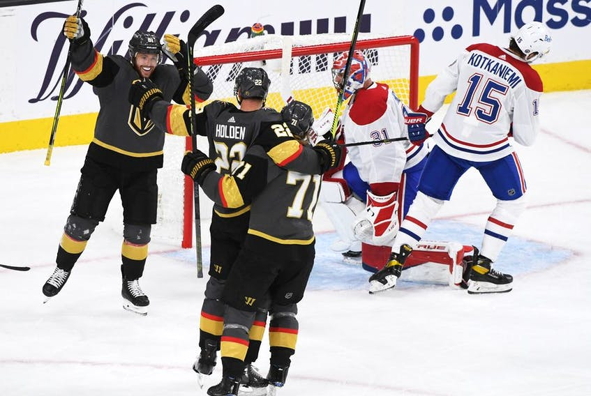 Nick Holden #22 of the Vegas Golden Knights celebrates with Jonathan Marchessault #81 and William Karlsson #71 after scoring a goal in the third period against the Montreal Canadiens during Game One of the Stanley Cup Semifinals at T-Mobile Arena on June 14, 2021 in Las Vegas, Nevada.