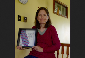 Wolfville children's author Jan Coates with the framed, autographed pink and blue striped necktie she received as a recipient of the Dr. Strang Community Hero Award. CONTRIBUTED