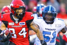 Calgary Stampeders Reggie Begelton takes off with the ball under pressure from Micah Awe of the Toronto Argonauts during CFL football in Calgary on Thursday, July 18, 2019. Al Charest/Postmedia