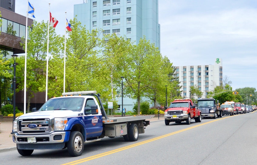 A convoy of tow trucks and flatbeds made its way through Sydney on Tuesday to express their concerns over a proposed tow truck licensing bylaw that industry owners and operators say is unfair and impractical. DAVID JALA/CAPE BRETON POST
