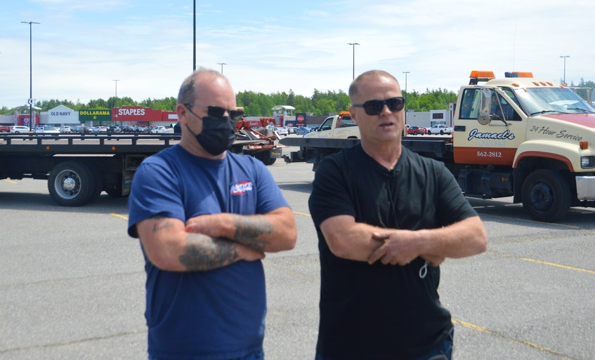 Tow truck owners Ronnie Smith, left, and Frank Campbell speak with members of the local news media on Tuesday prior to a rally of unity that saw some 20 tow trucks and flatbeds parade through Sydney on their way to city hall. DAVID JALA/CAPE BRETON POST