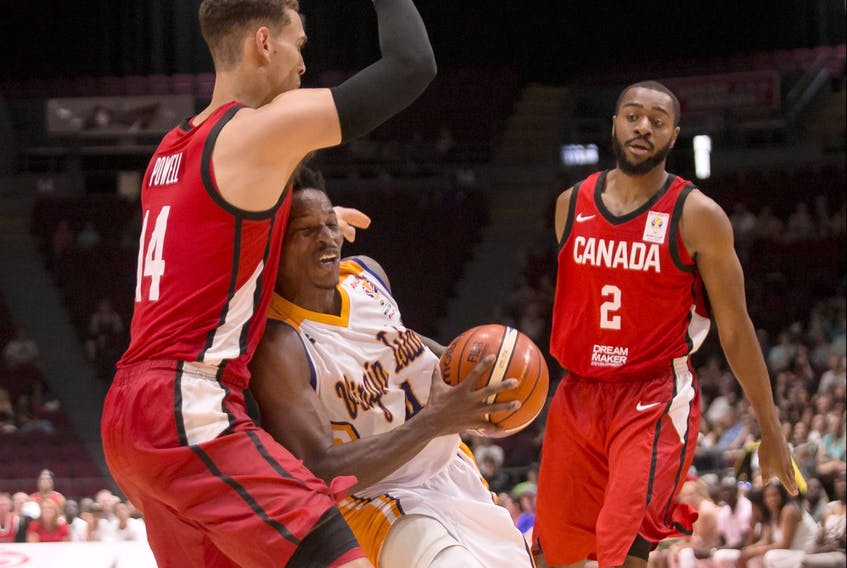 Team Virgin Islands' Georgio Milligan (4) tries to get through the defence of Team Canada's Dwight Powell (14) and Aaron Best (2) during FIBA World Cup qualifier action in 2018.