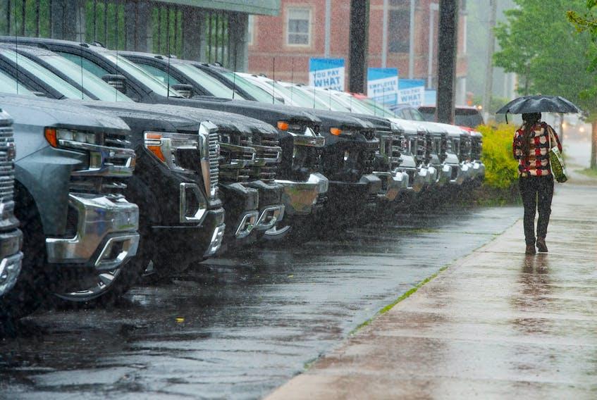 A pedestrian walks past the O'Regan's Chevy dealership on Robie St. on a rainy Tuesday, June 15, 2021. Ryan Taplin - The Chronicle Herald