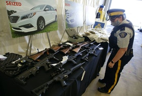 The RCMP's federal serious and organized crime unit has charged 14 people with 100 offences in connection with an 11-month investigation into a drug trafficking ring in Halifax Regional Municipality. Police seized a significant quantity of drugs, firearms and money. Some of the weapons and some of 122 lbs of cannabis products are shown on display at RCMP headquarters in Dartmouth Wednesday.