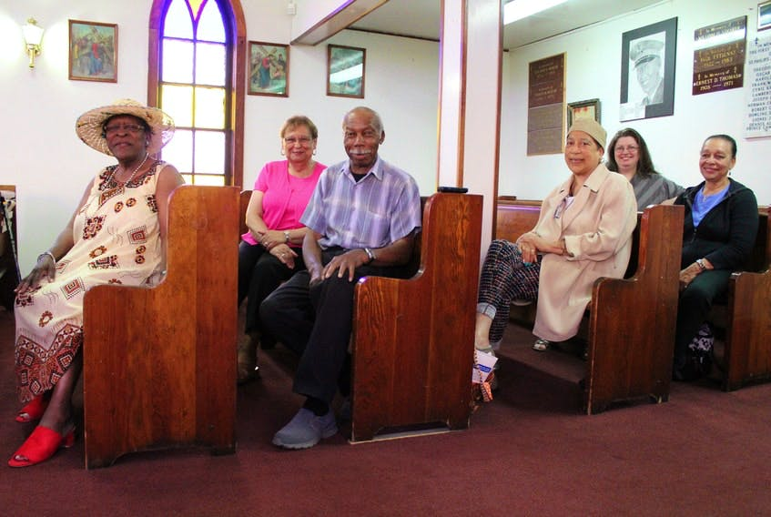 Some of the members of the congregation and a supporter of St. Philip's African Orthodox Church in Whitney Pier sit inside the pews of the church in this 2018 file photo. From left, are Monica Broomes, Iris Crawford, Whitfield Best, Rev. Mother Phyllis Marsh-Jarvis, Whitney MacEachern and Yvonne Stephenson. Nikki Sullivan/Cape Breton Post