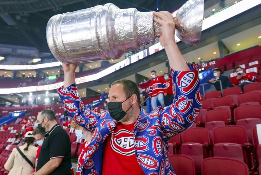 Canadiens fan Andy Mein hoists a Stanley Cup that he made while attending a second-round playoff game against the Winnipeg Jets at the Bell Centre.