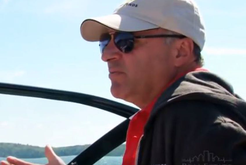 Businessman Kevin O'Leary behind the wheel of one of his boats on Lake Joseph.