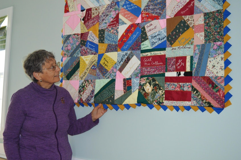 Ellen Cudmore, president of the Brackley Beach Women's Institute, shows one of the many quilts that hangs on the walls inside the Brackley Beach Community Centre. - Dave Stewart