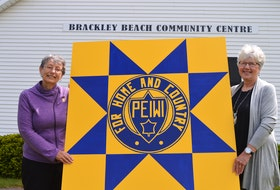 To help the Brackley Beach Women's Institute celebrate its 75th anniversary, group member Dorothy Clerk, painted this large barn quilt that will be installed on the outside of the Brackley Beach Community Centre, just above the sign in the background. With her is Ellen Cudmore, president of the local WI chapter.
