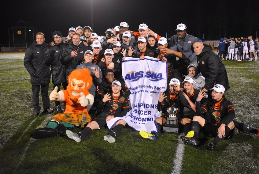 In this 2019 file photo, the Cape Breton Capers men's soccer team is shown with the Atlantic University Sport championship banner and trophy following their 2-0 overtime win over the St. Francis Xavier X-Men in the league final at Cape Breton Health Recreation Complex Turf. The Capers will open the 2021 season in September and will host the AUS championship in November in Sydney. JEREMY FRASER • CAPE BRETON POST