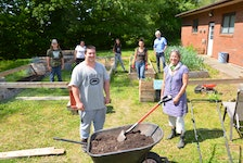 Valley Community Learning Association (VCLA) youth mentor and tutor Lucas Hatt and co-ordinator of experiential learning Tracy Horsman working in a recently-planted kitchen garden with other members of the VCLA team. KIRK STARRATT
