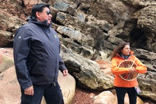 Clifford Paul, a guide who has made close to 200 trips to Kluskap's Cave, tells the legend of Kluskap and the Stone Maidens as he and Tara Lewis look out over the Atlantic Ocean to the Bird Islands. ARDELLE REYNOLDS/CAPE BRETON POST