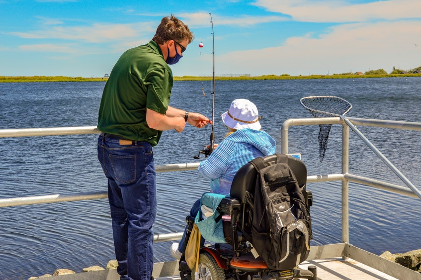 Port Morien Wildlife Association president Jeff McNeil shows disability advocate consultant Marcie Shwery-Stanley how to fish.