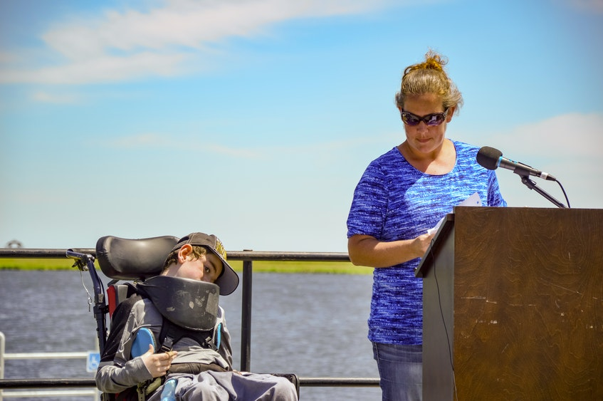 Nichol MacNeil speaks to the crowd at the event while her son Devon MacNeil, who has cerebral palsy, looks on. - Jessica Smith