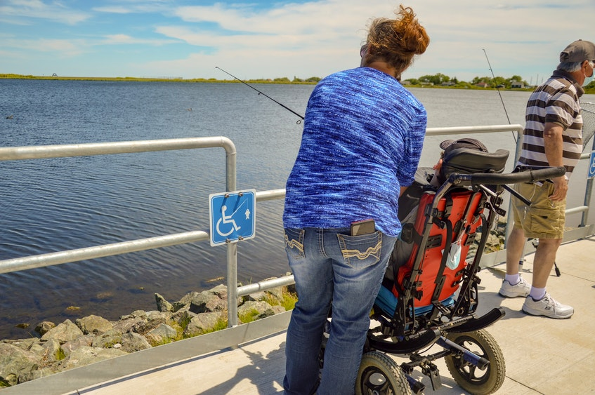Nichol MacNeil helps her son, Devon MacNeil, with a fishing pole, at the accessible fishing site.