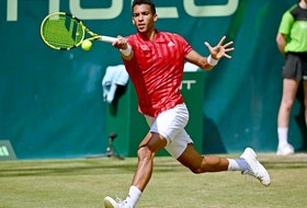Félix Auger-Aliassime plays a forehand in his match against Roger Federer of Switzerland at Noventi Open on June 16, 2021, in Halle, Germany.