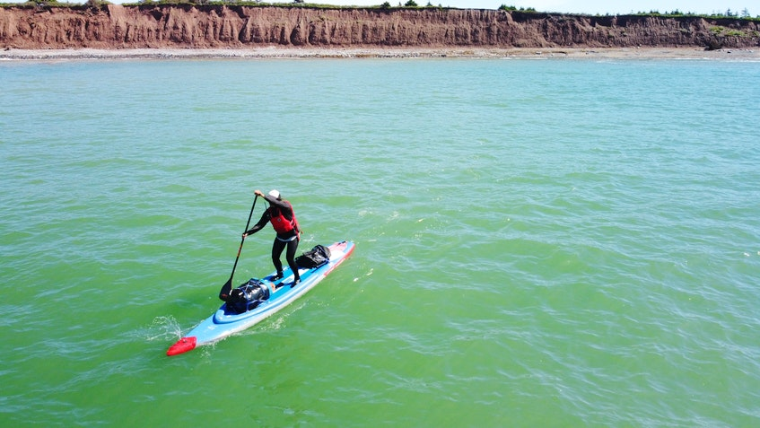 """Mariele Guerrero on her stand-up paddleboard. Wind and weather likely pose more of a problem than sharks, she said. """"And ultimately, I think on most outdoor adventures one of the greatest risks is yourself, just in terms of keeping an open mind, staying present, staying aware, not letting emotions or fear cloud your judgment.""""- Eric Wynne"""