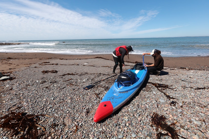 Mariele Guerrero and her boyfriend Dan Heywaid prepare her stand-up paddleboard for the next leg of the voyage after making a stop at Half Island Point, near Lawrencetown on Friday. - Eric Wynne