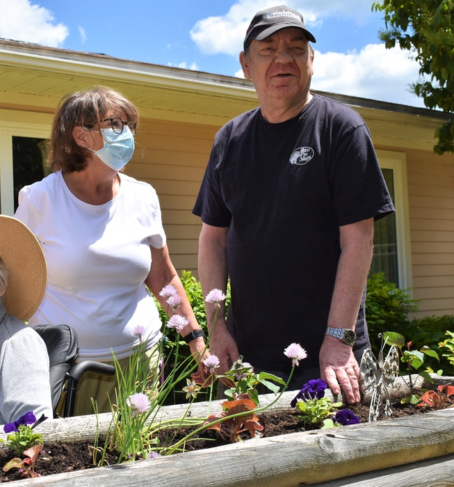 Elk Court staff member Helen Dearman and resident Wray White chat while standing next to a flower box White planted at the start of the growing season. - Richard MacKenzie