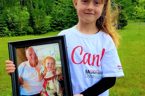 Lily MacDonald, pictured here in the last in-person fundraising walk for Muscular Dystrophy in 2019, holds a picture of her beloved grandfather, the late Bernie McKeough. While COVID has meant that virtual events had to be held the past two years, Lily remains dedicated to raising funds in her grandfather's memory.