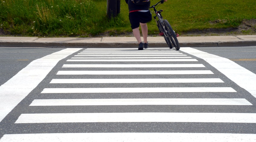 A pedestrian uses a crosswalk on a four-lane section of the Conception Bay Highway near the manuels river interpretation centre Friday afternoon.— Keith Gosse/The Telegram