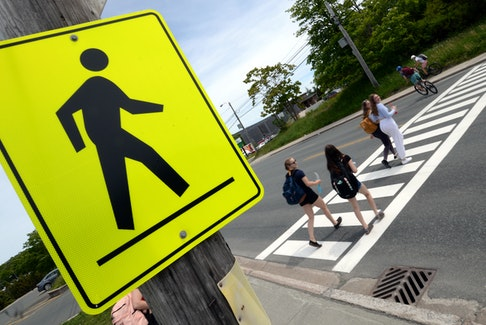 Pedestrians use a crosswalk on a four-lane section of the Conception Bay Highway near the Manuels River Interpretation Centre Friday afternoon. Keith Gosse • The Telegram