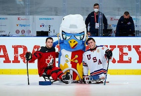 Canadian defenceman Liam Hickey (left) of St. John's and American star Brody Roybal pose with the tournament mascot prior to their opening game Saturday at the world para-hockey championship in Ostrava, Czech Republic. Roybal would score for the defending champion Americans, but Hickey — who assisted on the game's opening tally — would prevail for a 2-1 victory.