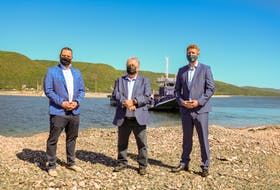 Minister of Education and Early Childhood Development Derek Mombourquette, left, Minister of Transportation and Active Transit Lloyd Hines, centre, and Premier Iain Rankin, right, stand in front of the Englishtown Ferry after the announcement. JESSICA SMITH/CAPE BRETON POST