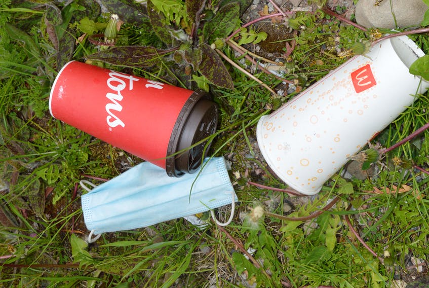 Two cups and a disposable mask are seen near a brook off Grand Lake Road in Sydney. Chris Connors/Cape Breton Post