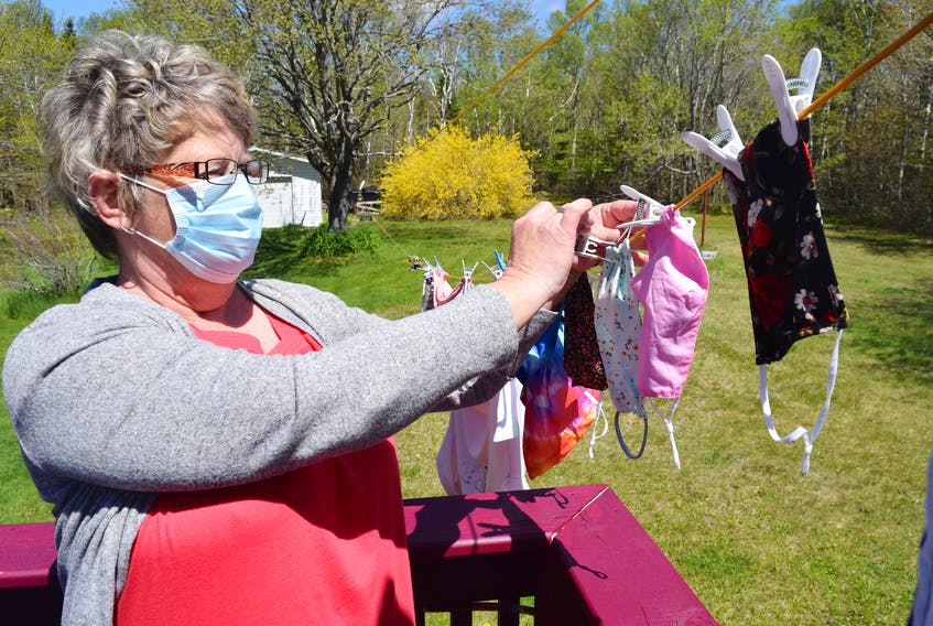 Linda Head of Grand Lake Road in Sydney hangs face masks after washing them by hand with detergent. Health officials say bacteria can live on masks and they must be washed regularly. Sharon Montgomery-Dupe • Cape Breton Post