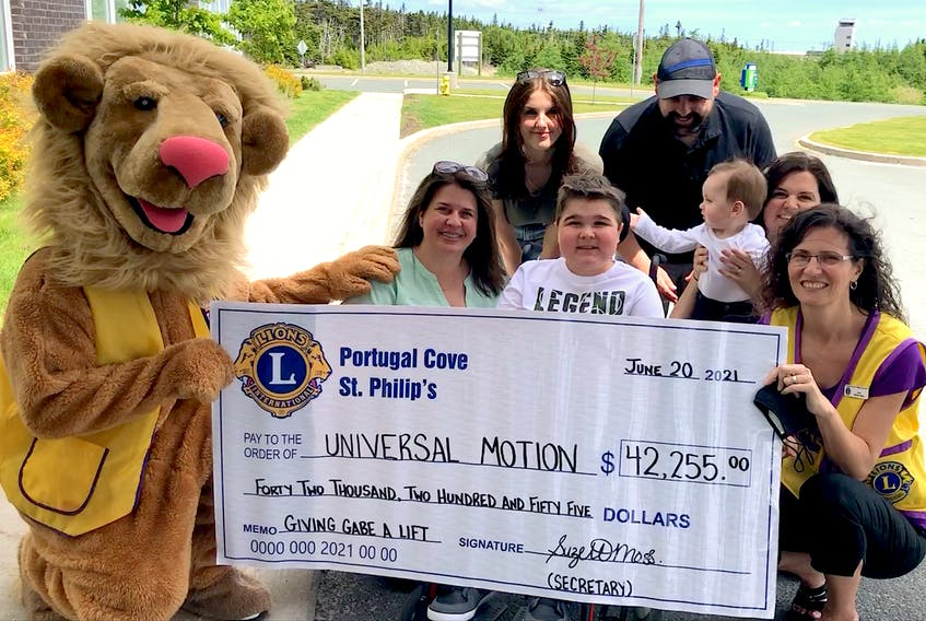 Suzette Moss (right) of the Portugal Cove-St. Philip's Lions club and club mascot Phillyco hold the cheque that was presented to Gabe Tucker and his family Sunday as the result of a fundraising effort by the Lions. The money will be used to purchase a lift for that will make it easier for Gabe, who has Duchenne Muscular Dystrophy, to enter and and exit his family's vehicle. Joining Gabe (centre) behind the cheque are (from left) his mother Lisa Tucker, his sister Allie Tucker, his dad Brad Squires, his brother Harrison Squires and his stepmother Anita Squires. — Joe Gibbons/The Telegram