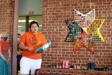 Cora Handrahan, left, and Sean Pellissier-Lush help present the eight-pointed star created by Corinne Chappell's Indigenous studies class at Colonel Gray High School.