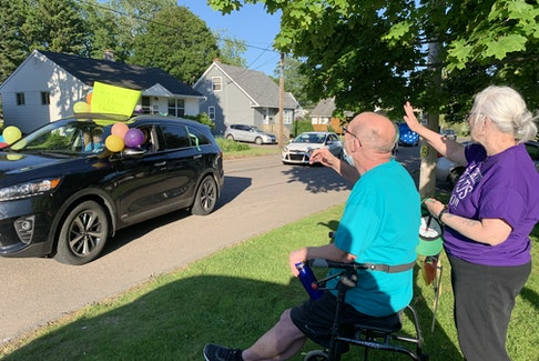 Charlie Chambers and his wife, Ruth Currie, greet vehicles passing their Westminster Avenue home in Amherst on Friday night. A popular teacher and basketball coach at Amherst Regional High School, Chambers spent more than 40 days in hospital after becoming ill with COVID-19.