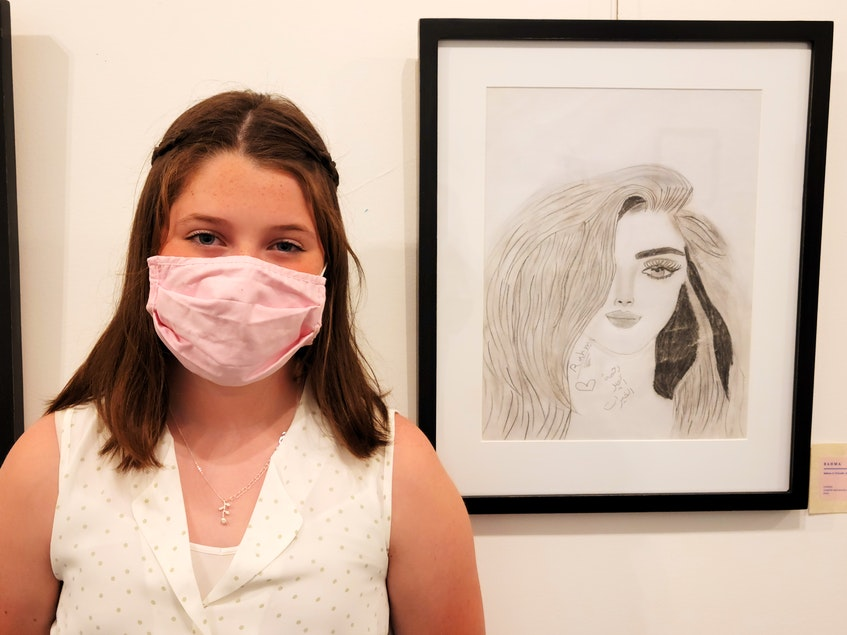 Lauren Graham stands beside one of Rahma's pictures at the Kings Playhouse art gallery. - Logan MacLean