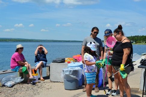 Seven-year-old Maxine Doucette puts on gloves to pick up garbage on the shoreline in Potlotek First Nation on Monday. The cleanup was a celebration of National Indigenous Peoples Day on Monday. ARDELLE REYNOLDS/CAPE BRETON POST