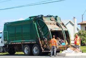 A crew picks up heavy garbage items in front of a home in New Waterford on Monday. IAN NATHANSON • CAPE BRETON POST