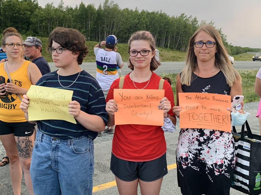 Protesters hold up signs voicing their displeasure with Premier Iain Rankin's decision earlier Tuesday not to fully reopen the border with neighbouring New Brunswick. - Darrell Cole
