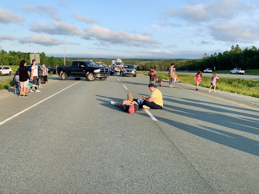 Two protesters lie on the pavement on Highway 104 near Exit 7 on Tuesday. The protest began shortly after 4 p.m. and lasted until after 9 p.m. - Darrell Cole