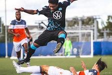 HFX Wanderers striker Akeem Garcia leaps over Forge FC defender Daniel Krutzen during a match at the Island Games last season in Charlottetown. - HFX WANDERERS