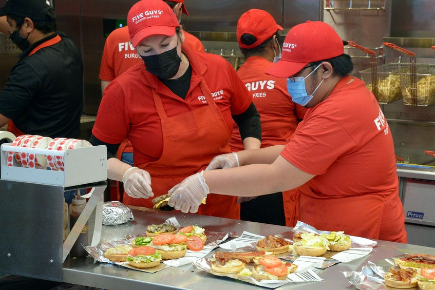 Employees at Five Guys Burgers and Fries restaurant at the Avalon Mall were kept busy as hundreds flocked to the store for the grand opening Tuesday. More than 60 people from this province were hired to work at the store. - Keith Gosse