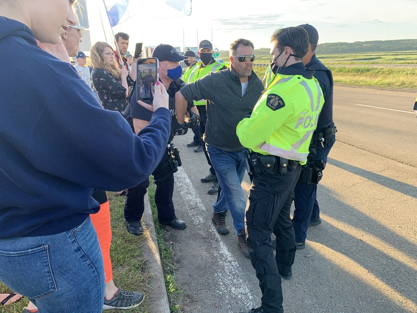A man is arrested as RCMP break up a blockade at the Nova Scotia border in Fort Lawrence, N.S., on Wednesday evening. The blockade lasted nearly 24 hours and stopped the flow of traffic across the border between Nova Scotia and New Brunswick. - Darrell Cole